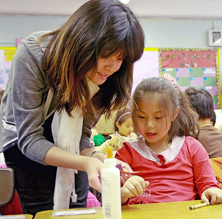 IRISH JEWEL: Joyce Chen teaches Chinatown P.S. 2 after school program's children to make Celtic bracelets as part of a lesson on New York City's Irish heritage. (Tara MacIsaac/The Epoch Times)