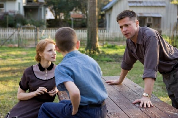"""a woman, a boy, and a man at a picnic table in """"The Tree of Life"""""""