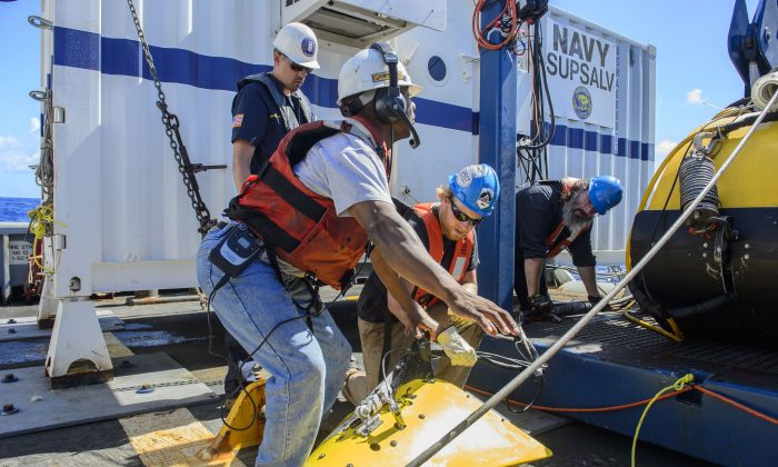 Contractors and Lt. Cmdr. Daniel Neverosky retrieve and secure the tow pinger locater aboard the USNS Apache on Oct. 24, 2015. USNS Apache departed Norfolk, Va., on Oct. 19, to begin searching for wreckage from the missing cargo ship El Faro. El Faro lost power and went down east of the Bahamas during Hurricane Joaquin. (John Paul Kotara II/Navy via AP)
