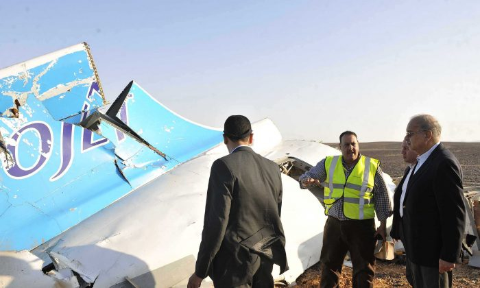 Sherif Ismail (R) looks at the remains of a crashed passenger jet in Hassana, Egypt on Saturday. (Suliman el-Oteify/Egyptian Prime Minister's Office via AP)