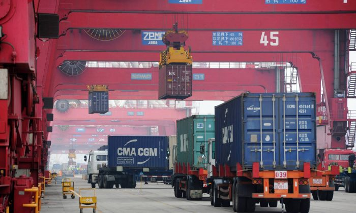 Trucks move shipping containers in the container pool of a seaport in Qingdao in eastern China's Shandong Province on July 1, 2015. (Chinatopix via AP)
