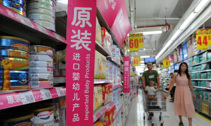 A family selecting baby formula in the imported baby products section of a supermarket in Beijing, on Aug. 4, 2013. (STR/AFP/Getty Images)