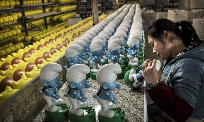 Chinese workers paint unfinished licensed ceramic 'Smurfs' at the Shunmei Group (SMG) ceramics factory during a tour on December 7, 2014 in Dehua, Fujian Province, China. (Kevin Frayer/Getty Image)