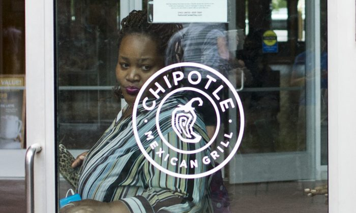 A woman walks out of a Chipotle restaurant in Washington, DC on September 9, 2015. (Andrew Caballero-Reynolds/AFP/Getty Images)