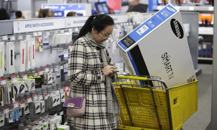 A customer uses her mobile phone as she shops for electronics and other items at a Best Buy on November 27, 2015 in Skokie, Ill.,  (Photo by Joshua Lott/Getty Images)