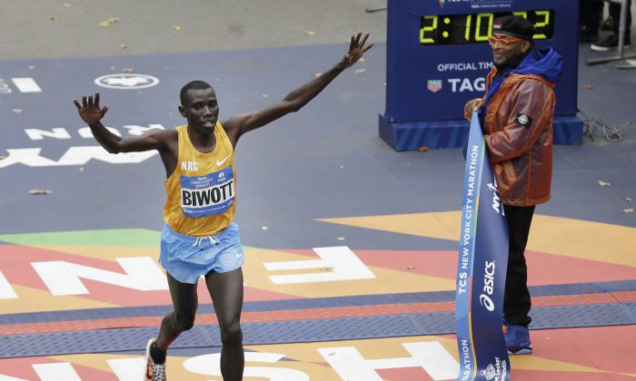 Stanley Biwott of Kenya (L) crosses the finish line first in the men's division at the 2015 New York City Marathon in New York, Sunday, Nov. 1, 2015.  (AP Photo/Seth Wenig)