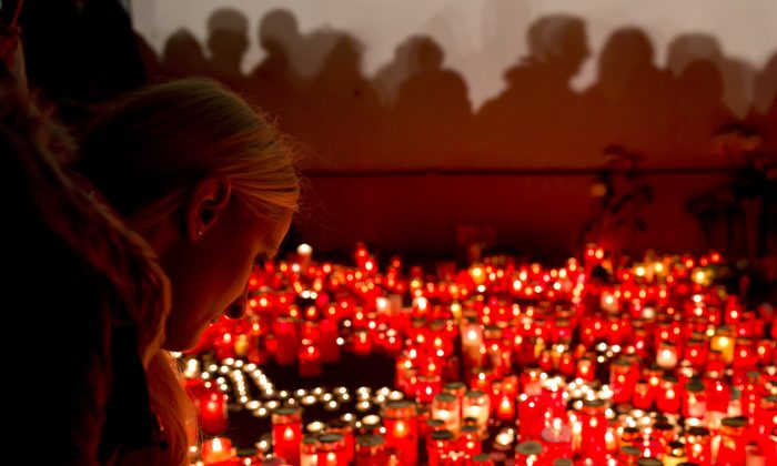 A girl lights candles outside the compound that housed the nightclub where a fire occurred in the early morning hours in Bucharest, Romania, Saturday, Oct. 31, 2015. Hundreds of young people had gone clubbing at the hip Colectiv nightclub Friday night to enjoy a free concert by the Goodbye to Gravity metal band but the evening ended in horror, as the inferno caused a panic that killed tens of people and injured many others. (AP Photo/Vadim Ghirda)