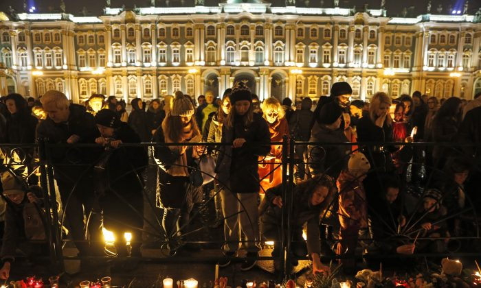 People gathered to light candles during a day of national mourning for the plane crash victims at Dvortsovaya (Palace) Square in St. Petersburg, Russia, on Sunday, Nov. 1, 2015.  (AP Photo/Dmitry Lovetsky)