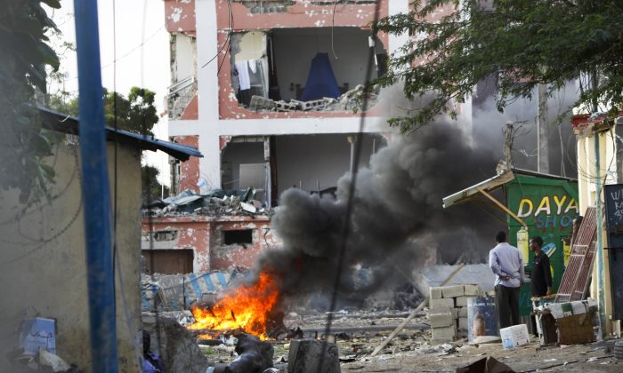 Somali men watch as fires burn amidst the destruction outside the Sahafi Hotel in Mogadishu, Somalia, Sunday, Nov. 1, 2015. A Somali police officer says an explosion followed by heavy gunfire has been heard, thought to have been caused by a suicide car bomb, at the hotel often frequented by Somali government officials and business executives. (AP Photo/Farah Abdi Warsameh)