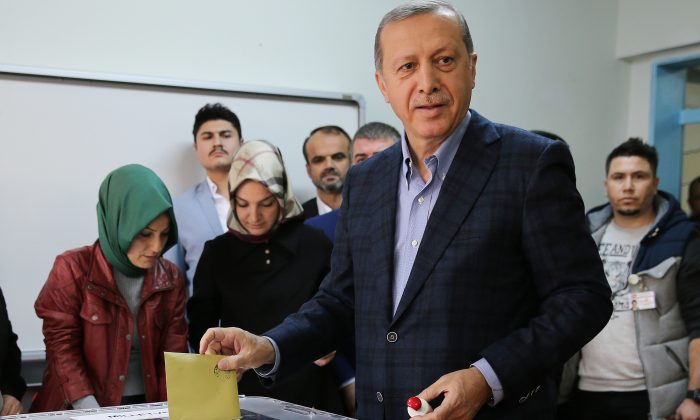 Turkey's President Recep Tayyip Erdogan casts his vote at a polling station, in Istanbul, Sunday, Nov. 1, 2015. (AP Photo/Hussein Malla)