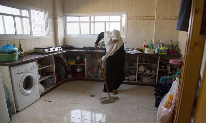 Um Alabed al-Zaza mops her new kitchen in a house that was completely destroyed during the last summer's war between Israel and Hamas, Gaza City, on Oct. 28, 2015. The four story house belonging to al-Zaza family is being rebuilt ad part of the family has moved in into renovated ground floor apartment. (AP Photo/Adel Hana)