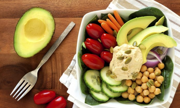 Healthy lunch bowl with avocado, hummus and fresh vegetables, overhead scene on wooden table