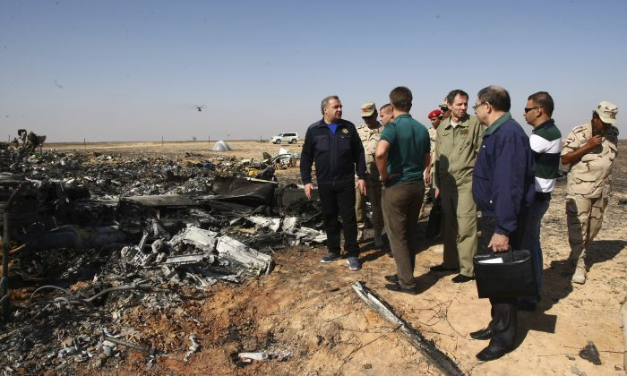 Russian Emergency Situations Minister Vladimir Puchkov (L) talks with Russian Transport Minister Maxim Sokolov (5R), as they inspect the wreckage in Hassana, Egypt, on Nov. 1. (Maxim Grigoriev/Russian Ministry for Emergency Situations via AP)