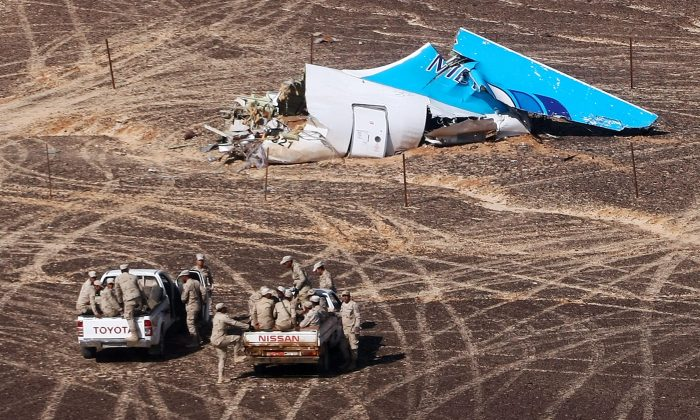 Egyptian Military on cars approach a plane's tail at the wreckage of a passenger jet bound for St. Petersburg in Russia that crashed in Hassana, Egypt, on Sunday, Nov. 1, 2015. (Maxim Grigoriev/Russian Ministry for Emergency Situations via AP)