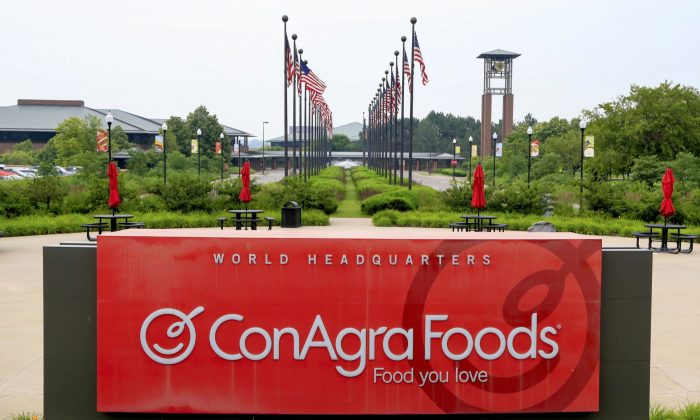 Flags fly over ConAgra Foods world headquarters in Omaha, Neb., on June 30, 2015. ConAgra Foods Inc. is selling its private label operations to TreeHouse Foods Inc. for about $2.7 billion as part its plan to focus more on name brands including Chef Boyardee and Slim Jim. The deal comes one month after ConAgra said it will cut 1,500 jobs, or about 30 percent of its office-based workforce, and move its headquarters to Chicago from Omaha, Nebraska. (AP Photo/Nati Harnik)