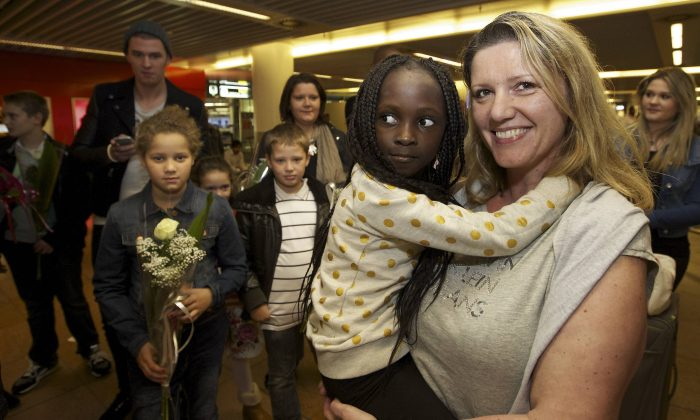 Belgian Laurence Senechal (R) arrives at Brussels National Airport in Zaventem from Kinshasa on Aug. 31, 2014, where she was greeted by her adopted daughter, Imany. (Nicolas Maeterlink/AFP/Getty Images)