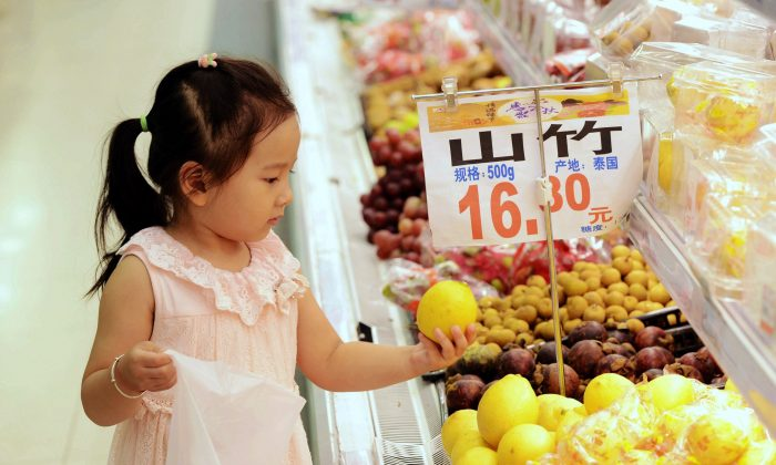 A young Chinese girl selects fruit at a supermarket in Qingdao, east China's Shandong Province on September 10, 2015. (STR/AFP/Getty Images)