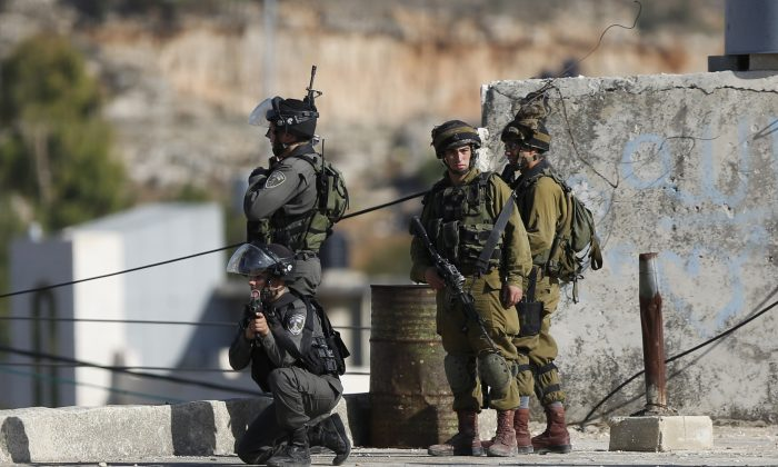 Israeli security troops take positions at the scene of a stabbing attempt, in the Beit Einun junction east of the West Bank city of Hebron, Sunday, Nov 1, 2015. (AP Photo/Nasser Shiyoukhi)