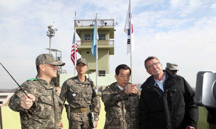 U.S. Defense Secretary Ash Carter, right, and South Korean Defense Minister Han Min Koo, second from right, look towards North Korea at an observation post near the border village of Panmunjom, which has separated the two Koreas since the Korean War, in Paju, South Korea, Sunday, Nov. 1, 2015. (Korea Pool Photo via AP)