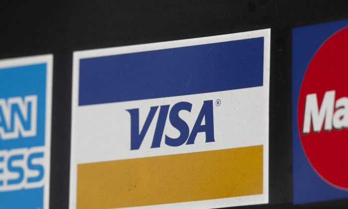 A sign for Visa is shown in New York on March 19, 2012. Visa plans to buy Visa Europe in a cash-and-stock deal that could be worth more than $23 billion. (AP Photo/Mark Lennihan)