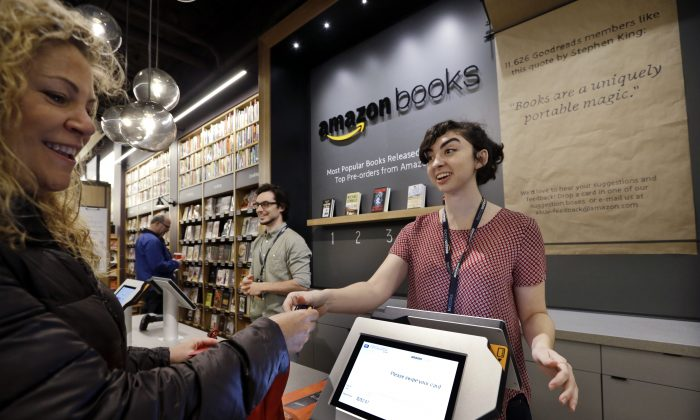 A customer Kmakes one of the first purchases at the opening day for Amazon Books, the first brick-and-mortar retail store for online retail giant Amazon, in Seattle on Nov. 3. (AP Photo/Elaine Thompson)
