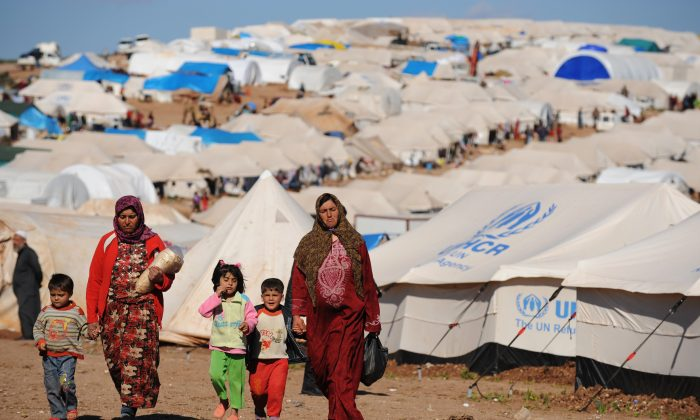 Syrian internally displaced people walk in the Atme Camp, along the Turkish border, in the northwestern Syrian province of Idlib, on March 19, 2013. (Bulent Kilic/AFP/Getty Images)