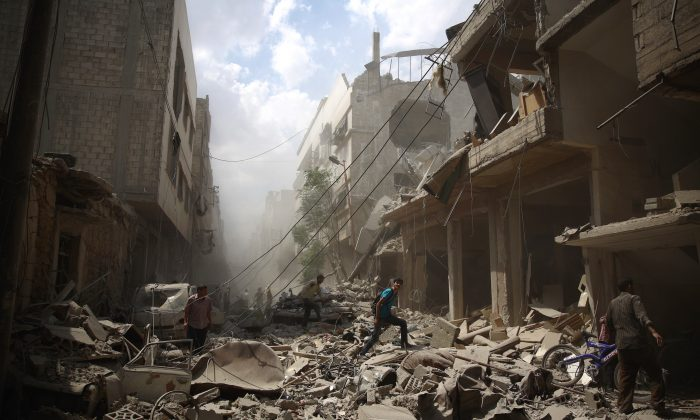 Syrians walk amid the rubble of destroyed buildings following reported air strikes by the Assad regime forces in the rebel-held area of Douma, east of the capital Damascus, on Aug. 30, 2015. (Abd Doumany/AFP/Getty Images)
