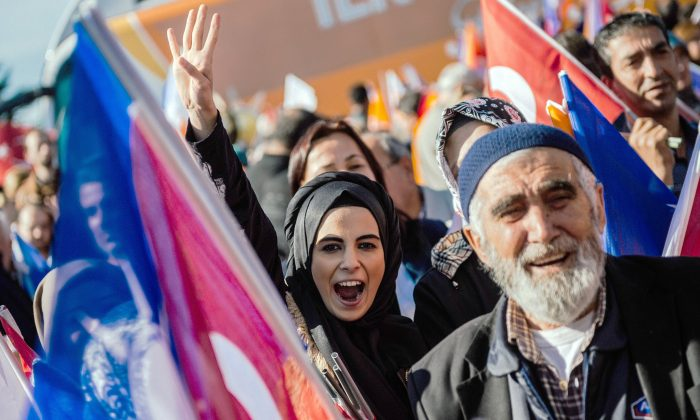 A Turkish woman makes a rabia sign as supporters wait for the Turkish Prime Minister Ahmet Davutoglu at the Istanbul Ataturk airport, on Nov. 3, 2015. Turkey's long dominant Justice and Development Party (AKP) scored a stunning election success at the weekend with a vote that returned it to single-party rule after months of political uncertainty. The result is likely to bolster strongman President Recep Tayyip Erdogan as he seeks to expand his powers, but analysts warn it could further exacerbate deep rifts in Turkish society. (Ozan Kose/AFP/Getty Images)