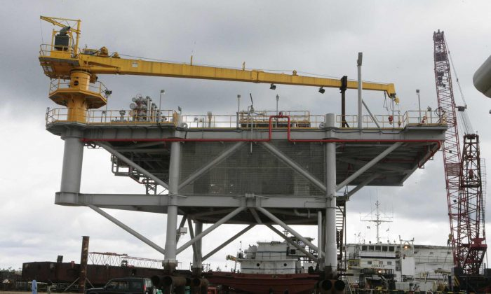 The Mejiriser platform located in Ogbogoro community, on the outskirt of Port Harcourt, appears on Oct. 12, 2006, as it was inaugurated by then Nigerian President Olusegun Obasanjo near the southern oil city of Port Harcourt. The nation's first floating flow station—built by the local firm Transcoastal Woas at a cost of $3.1 million—is a joint venture project between state-run Nigerian National Petroleum Corporation (NNPC) and Chevron. The four-legged platform, looking like a bridge, with 520 metric tons topside, has a production manifold and two hydro-carbon drain vessels. (Wole Emmanuel/AFP/Getty Images)