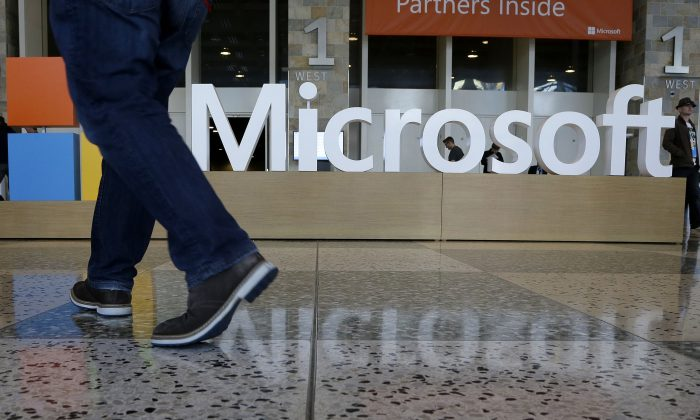 A man walks past a Microsoft sign set up for the Microsoft BUILD conference at Moscone Center in San Francisco, on April 28, 2015. Starting next year, Microsoft will cut the free space it offers through its OneDrive service to 5 gigabytes, down from 15 gigabytes now. Microsoft says the new allotment is enough for about 6,600 Office documents or 1,600 photos. (AP Photo/Jeff Chiu)