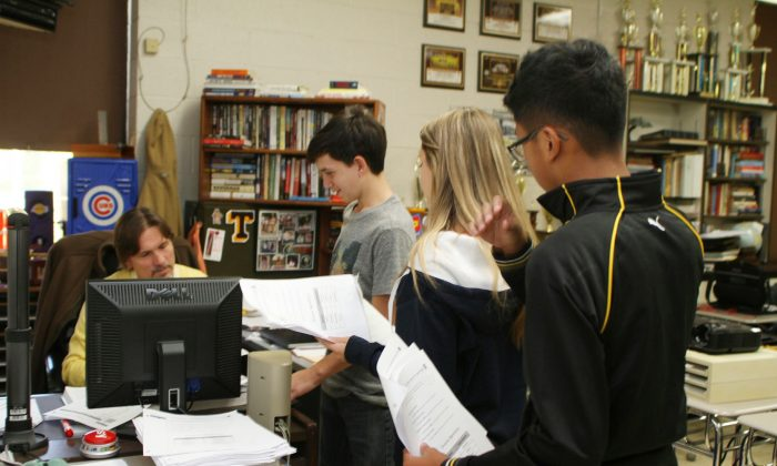 Eighth grade algebra students line up to speak to teacher Mark Olsen in his flipped classroom at Thomaston High School in Thomaston, Conn., on Oct. 9, 2015. The flipped teaching model does just that—flip the order in which students pursue their studies. Rather than hear lessons in class and do homework after school, students watch a lecture featuring new content at home, then work through exercises and projects during class. Thomaston eighth-graders are taught at Thomaston High School. (Laraine Weschler/Republican-American via AP)