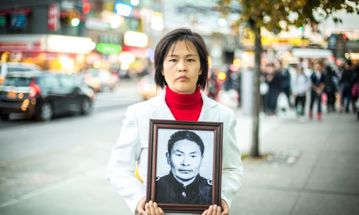 Jiang Li in Flushing, Queens, on Nov. 1, 2015, holds a photo of her father who was killed by the Chinese Communist Party in China for practicing Falun Gong. (Benjamin Chasteen/Epoch Times)