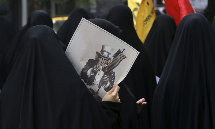 A female Iranian demonstrator holds a poster showing a caricature of Uncle Sam during an annual anti-U.S. rally in front of the former U.S. Embassy in Tehran, marking 36th anniversary of the seizure of the embassy by militant Iranian students, Iran, Wednesday, Oct. 4, 2015. The annual state-organized rally Wednesday drawing greater attention this year, as Iranian hardliners are intensifying a campaign to undermine President Hassan Rouhani's outreach to the West following a landmark nuclear deal reached with world powers in July. (AP Photo/Vahid Salemi)