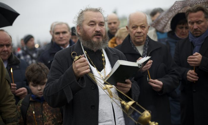 An Orthodox priest conducts an improvised religious service in memory of the plane crash victims in St. Petersburg, Russia, on Wednesday, Nov. 4, 2015. (AP Photo/Ivan Sekretarev)