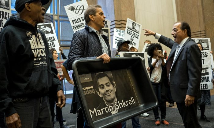 AIDS activists and others, carrying an image of Turing Pharmaceuticals CEO Martin Shkreli in a makeshift cat litter pan, are asked to leave the lobby of 1177 6th Ave. in New York, during a protest highlighting pharmaceutical drug pricing, on Oct. 1, 2015. (AP Photo/Craig Ruttle)