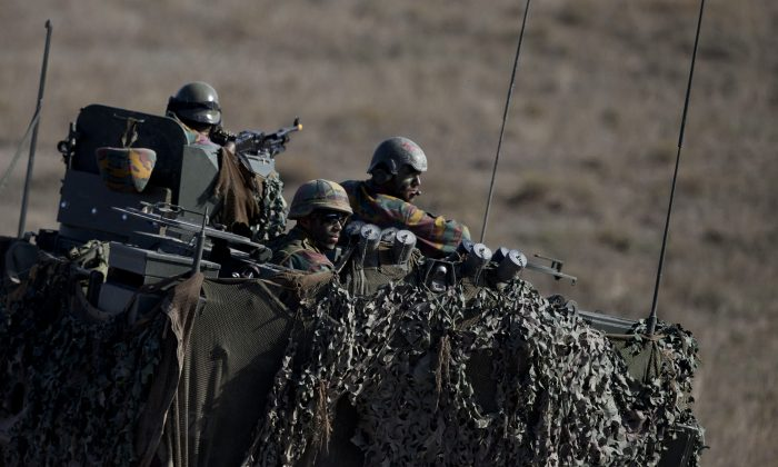 Belgian troops in a camouflaged vehicle during a NATO military demonstration in Zaragoza, Spain, on Nov. 4. (AP Photo/Abraham Caro Marin)