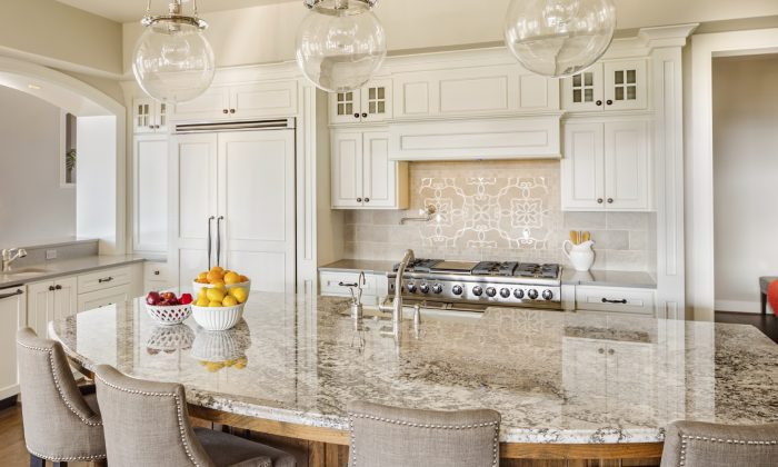 Hardwood floors, white cabinetry, and marble countertops create an attractive and functional kitchen that will stand the test of time. (hikesterson/iStock)