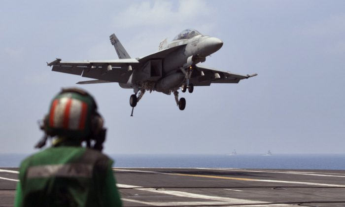 A U.S. Navy fighter jet approaches to land on the aircraft carrier USS Theodore Roosevelt (CVN 71), a missile cruiser and a nuclear-powered submarine during Exercise Malabar 2015, some 152 miles off eastern coast of Chennai, India, Saturday, Oct. 17, 2015. Naval warships, aircraft carriers and submarines from the U.S., India and Japan steamed into the Bay of Bengal on Saturday as they took part in joint military exercises off India's east coast, signaling the growing strategic ties among the three countries as they face up to a rising China. (AP Photo/Arun Sankar K.)