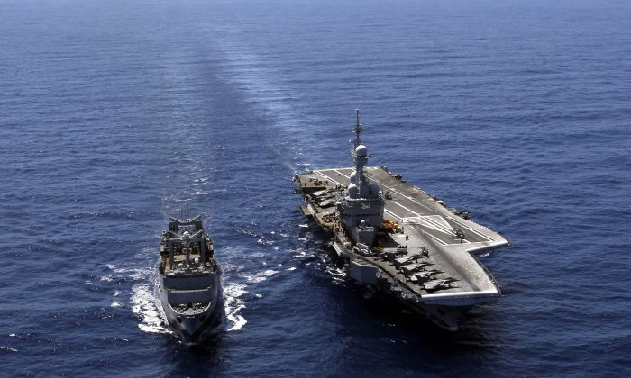 In this April 12, 2011 file photo, France's flagship Charles de Gaulle aircraft carrier, right, steams with resupply ship La Meuse, in the Golf of Sirte, off the Libyan coast. (AP Photo/Christophe Ena)
