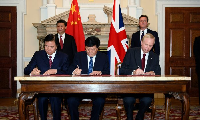 Chairman of oil and gas company PetroChina, Wang Yilin (L), Chairman of power company China Huadian Corporation, Li Quingkui (C), and Chief Executive of oil and gas company BP, Bob Dudley (R), sign contracts during a commercial contract exchange at the U.K.-China Business Summit in Mansion House, central London, on Oct. 21, 2015, on the second day of his state visit. Britain and China are set to seal business contracts worth billions on the second day of President Xi Jinping's state visit, including on Britain's first nuclear power plant in decades. (Leon Neal/AFP/Getty Images)