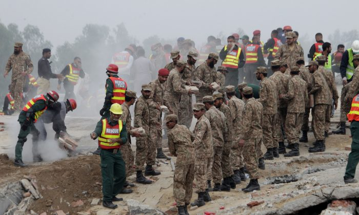 Pakistan army soldiers and volunteers take part in a rescue work in Lahore, Pakistan, Thursday, Nov. 5, 2015. (AP Photo/K.M. Chaudary)