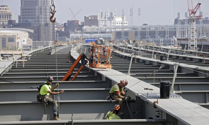 In this photo taken Aug. 30, 2013, ironworkers secure a cross member on a highway bridge under construction in Cleveland. The House has voted to continue transportation programs for six years with no significant increase in spending. That's despite warnings that the nation's roads, bridges and transit systems are falling apart.  (AP Photo/Mark Duncan)