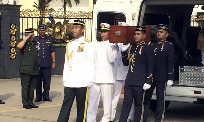 Malaysian troops carry a box with human remains recoved from the crash of a U.S. military transport plane in Malaysia during a military ceremony in Kuala Lumpur, Malaysia, Thursday, Nov. 5, 2015. After the military ceremony attended by U.S. Defense Secretary Ash Carter, the remains were to be flown to a Defense Department lab in Hawaii to attempt to positively identify them. (AP Photo/Robert Burns)