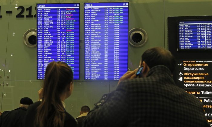 People look at an indicator board displaying flight information, at Pulkovo airport outside St.Petersburg, Russia, Friday, Nov. 6, 2015.  Russia announced Friday it will suspend all flights to Egypt until security is improved at its airports, the first sign of wariness from Moscow after days of resisting British and American warnings that a bomb planted by the Islamic State group may have brought down a Russian plane in the Sinai Peninsula last week. (AP Photo/Dmitry Lovetsky)