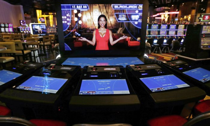 An automated dealer asks for players to take a seat at a black jack video slot machine on the floor of the Plainridge Park Casino, in Plainville, Mass., on June 23, 2015. The middle-aged Massachusetts State Lottery is nervously looking over its shoulder to see if the state's newborn casino industry will drain away some of the hundreds of millions it generates in profits each year for local cities and towns. (AP Photo/Charles Krupa)