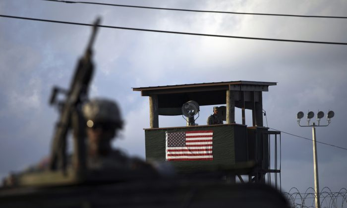 A U.S. trooper mans a machine gun in the turret on a vehicle as a guard looks out from a tower in front of the detention facility at Guantanamo Bay U.S. Naval Base, Cuba, on March 30, 2010. (AP Photo/Brennan Linsley)