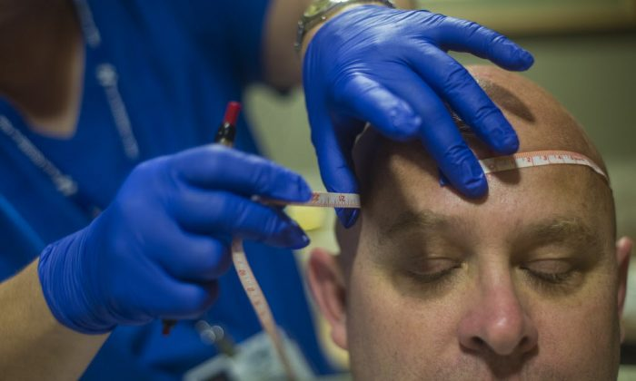 Registered sleep technician Elaine Sheely measures Daniel Gullickson's head for wire placement in Hanover Hospital's Sleep Lab in Hanover, Pa., on Sept. 1, 2015. (Clare Becker/The Evening Sun via AP)