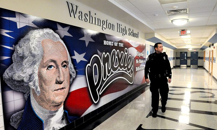 Washington police officer Todd Foreman—a Washington High School Resource officer—walks the hallways at school at part of his duties in Washington, Pa. Foreman, a city patrolman and detective who started at the district in 2004, says that forging relationships with students helps avoid or de-escalate potential problems. (Jim McNutt/Observer-Reporter via AP)