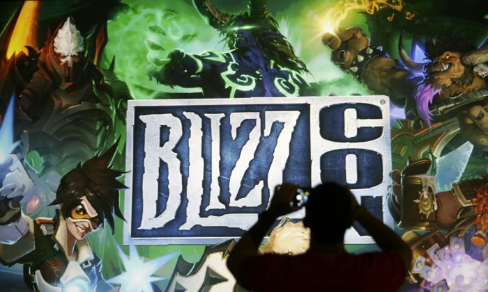 A man takes pictures of the BlizzCon sign at the opening ceremony of the convention, Friday, Nov. 6, 2015, in Anaheim, Calif. (AP Photo/Jae C. Hong)