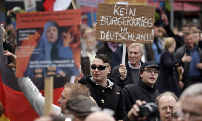 """People take part in a protest rally of the German party """"Alternative fuer Deutschland"""" (AfD, """"Alternative for Germany"""") in Berlin, Germany, Saturday, Nov. 7, 2015. Text on the poster in the background reads """"No civil war in Germany!"""" An anti-immigration party has staged a march in Berlin against the German government's migrant policies, with demonstrators chanting """"Merkel must go"""" and counter-protesters shouting """"Nazis out."""" (AP Photo/Michael Sohn)"""